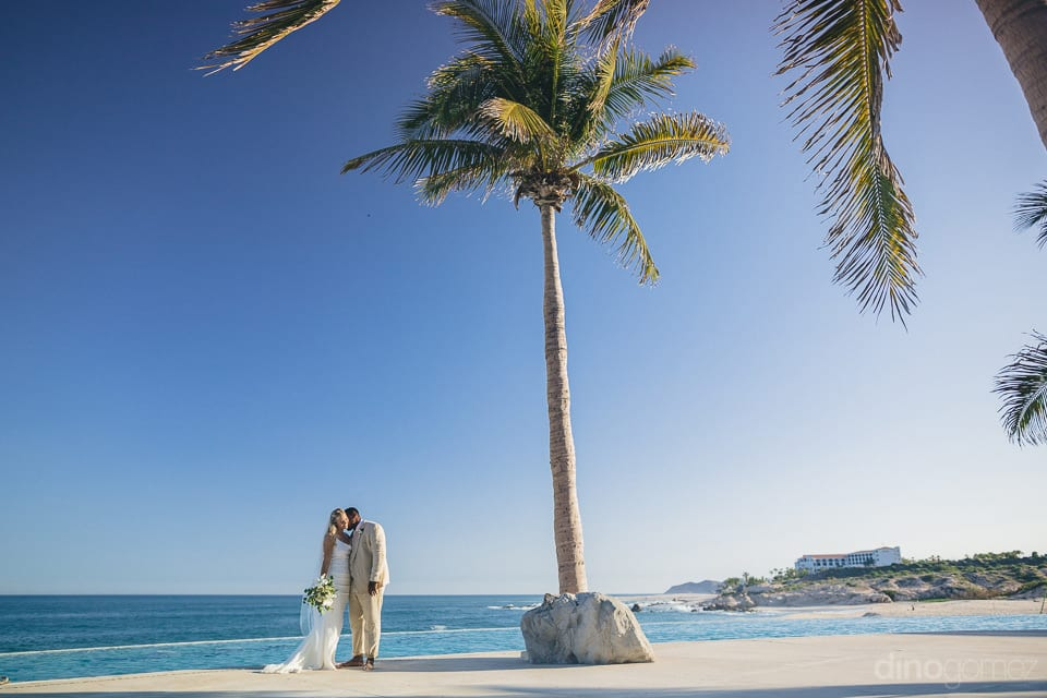 Gorgeous couple is kissing while standing under the beautiful palm tree along with the sea shore- Amber & Josh
