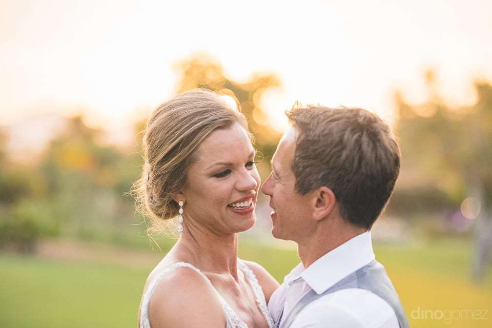 Lovely couple is smiling and looking deep into each others eyes in the beautiful farms- Heather & Ross