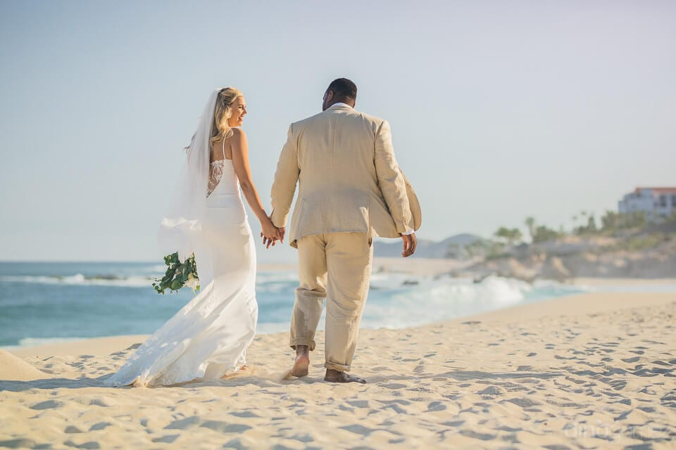The bride & groom are walking along the sea shore immidiately after the completion of wedding ceremonies- Amber & Josh