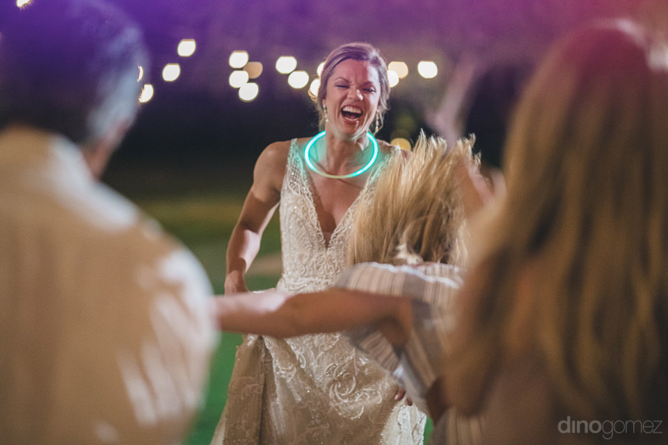 Pretty bride is wearing a glow band around her neck and laughing her heart out at the dance floor in the evening party- Heather & Ross