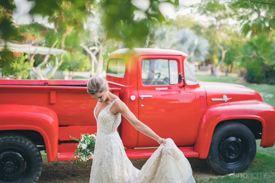 Pretty bride is giving a stunning pose for the camera infront of a vintage car- Heather & Ross