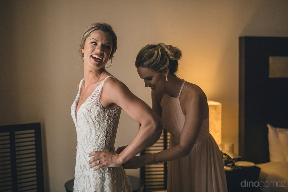 Bride is looking pretty in her wedding gown which is being set by a bridesmaid on her wedding day- Heather & Ross