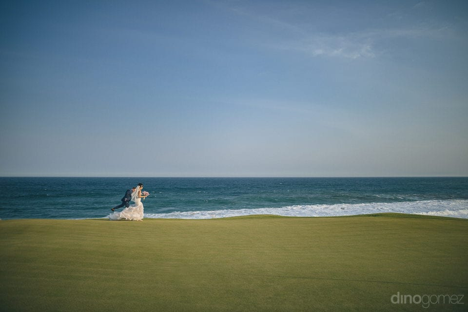 Beautiful bride & groom are running along the shore line of the blue watered sea- Jay & Drew
