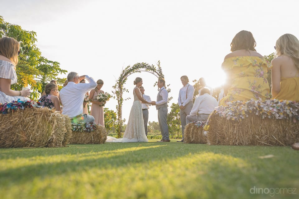 The image captures the wedding moment of the lovely couple while they are taking blessings to begin their new lives- Heather & Ross The picture captures the lovely moment of the couple taking blessings as husband & wife. The image is taken from the ground