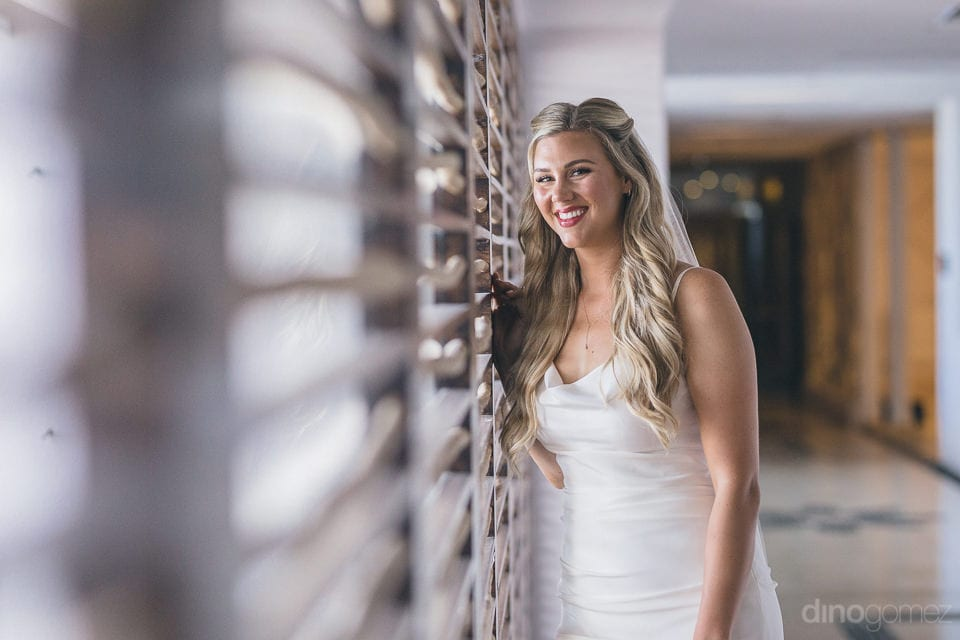 Lovely bride is leaning against a window and is posing with bright smile on her face for the camera- Amber & Josh