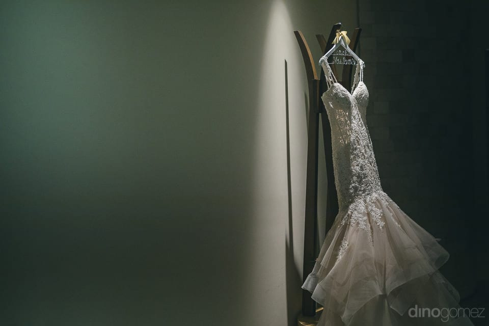 Beautiful white gown of the lovely bride is displayed on a wall inside a room in the palace- Jay & Drew