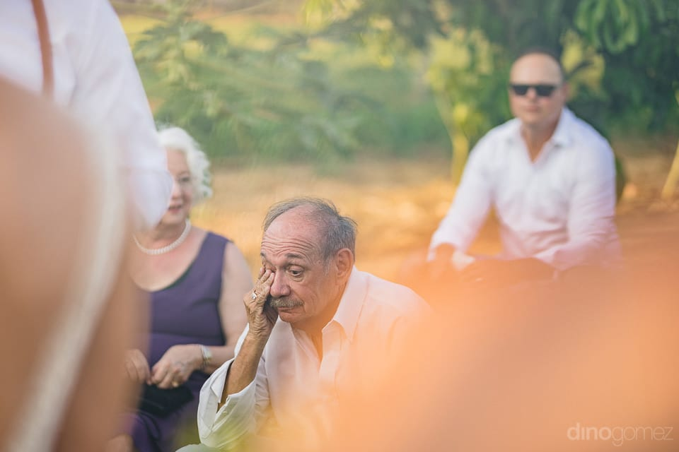 An elderly couple is wiping off something his eyes while attending the wedding ceremony of the couple- Heather & Ross
