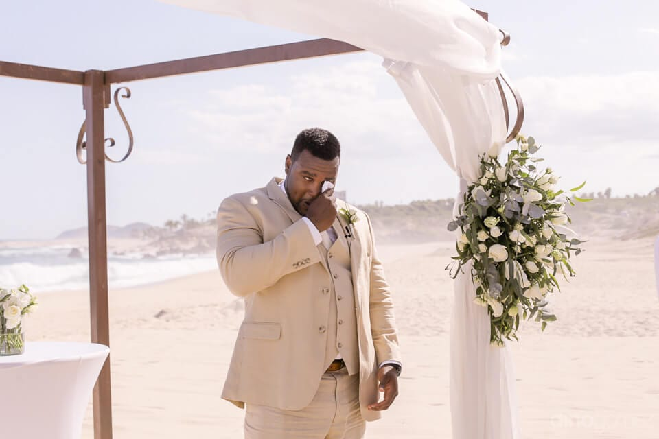 Handsome groom is dressed in his wedding suit is standing at the wedding stage and is wipping his eyes while the bride is arriving at the wedding stage- Amber & Josh