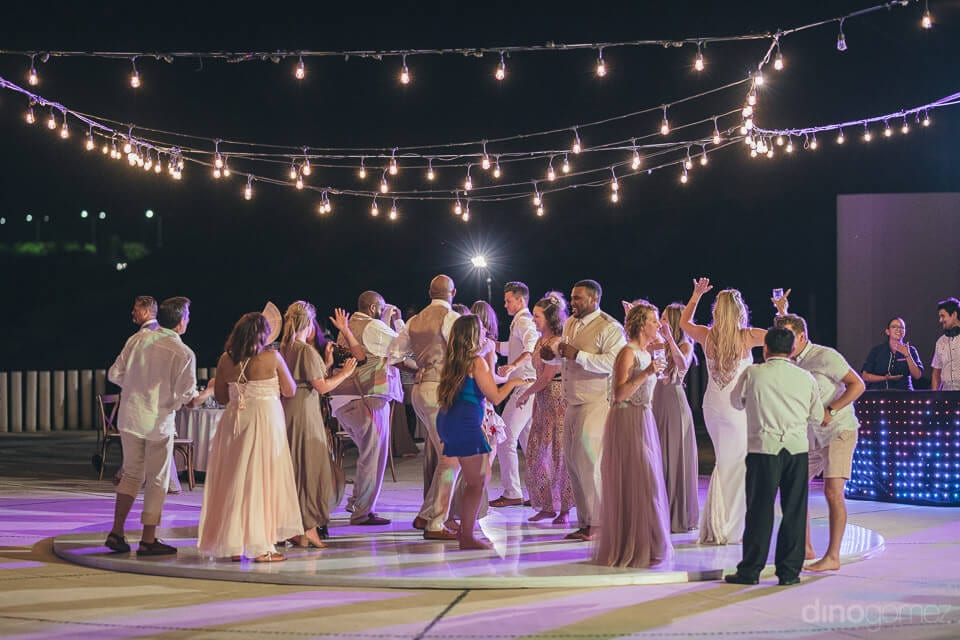A distant image capturing all the guests dancing together under the beautiful yellow lights at the evening reception party of the couple- Amber & Josh