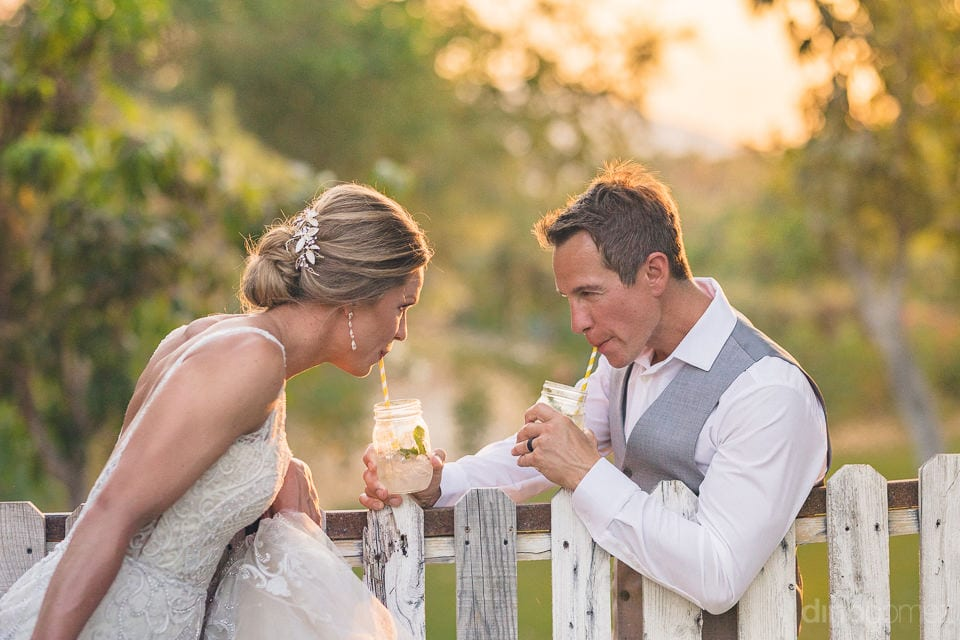 The bride and groom are taking sips from the glasses of drinks they are holding at the fresh green farms- Heather & Ross