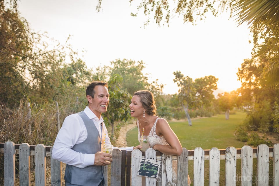 The newly married couple is laughing out loud while leaning against a wooden fence in the farm- Heather & Ross