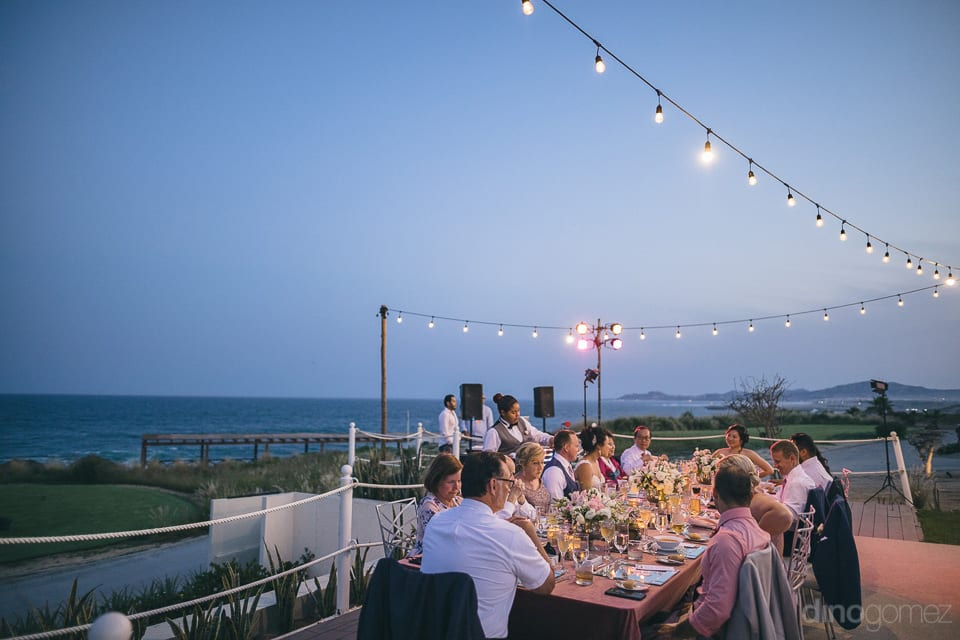 A beautiful beach side dinner is being enjoyed by all the guests at the reception party of the couple- Jay & Drew