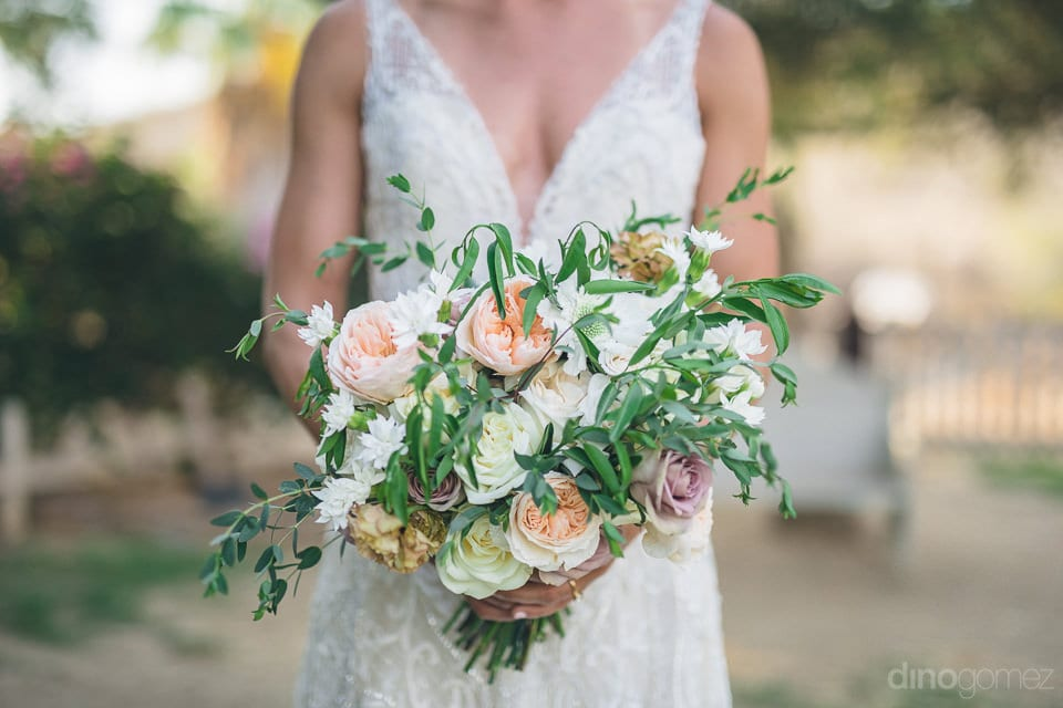 Bride can be seen holding a colorful bouquet of roses for her wedding- Heather & Ross