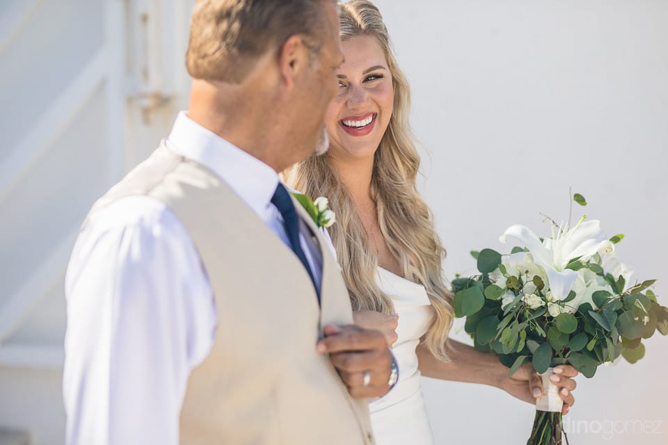 Pretty bride is smiling at the gentleman while looking at him walking towards the wedding stage- Amber & Josh