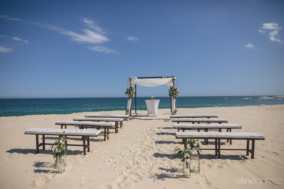 Wedding venue of the lovely couple is decorated with white flowers and white seats at the beach side- Amber & Josh