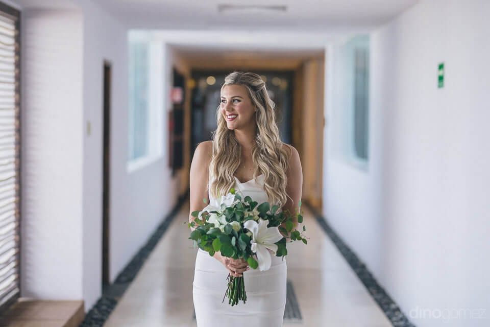 Lovely bride is looking amazing in her white silk gown and is holding her wedding bouquet while standing in a corridor- Amber & Josh