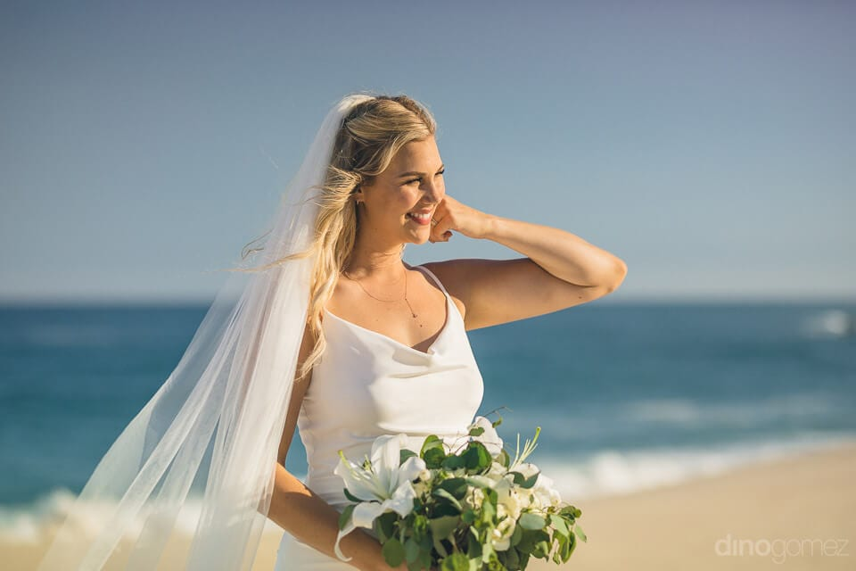 The bride is looking amazing in her wedding gown while posing for the camera at the beachside- Amber & Josh