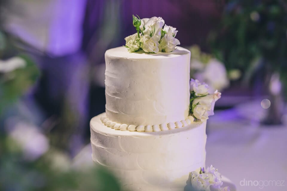 Delicious two-tier cake is placed on the top of the table and is decorated with white cream and roses- Amber & Josh