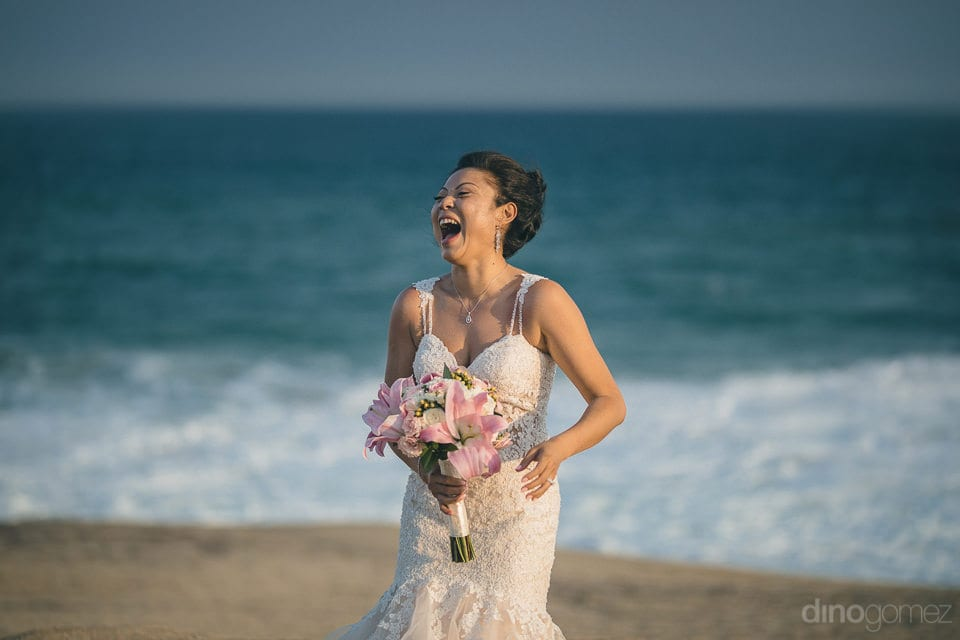 The bride is laughing loudly while standing next to the beautiful sea after her wedding- Jay & Drew