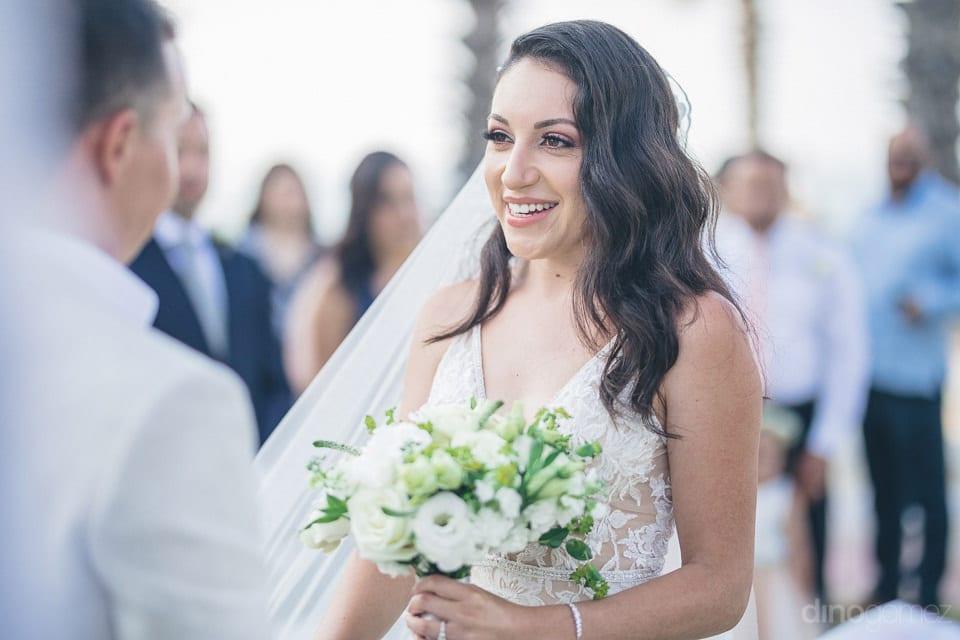 Picture captures the pretty bride smiling broadly while looking at the groom during the wedding ceremony- Christina & Steve