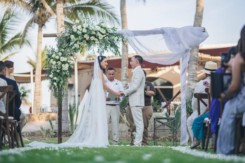 Gorgeous couple is standing on the lush green garden of the palace and is taking wedding oaths in the presence of the wedding guests- Christina & Steve