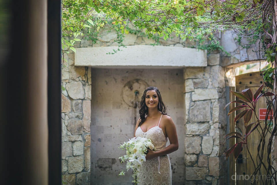 Lovely bride is standing infront of a beautiful wall of stones and is holding her wedding bouquet to pose for the camera- Nicole & Ryan