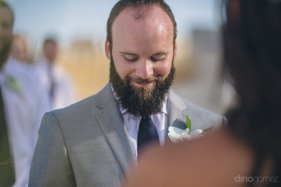 Picture captures the groom smiling and looking at something while standing next to the groom at the wedding stage- Nicole & Ryan