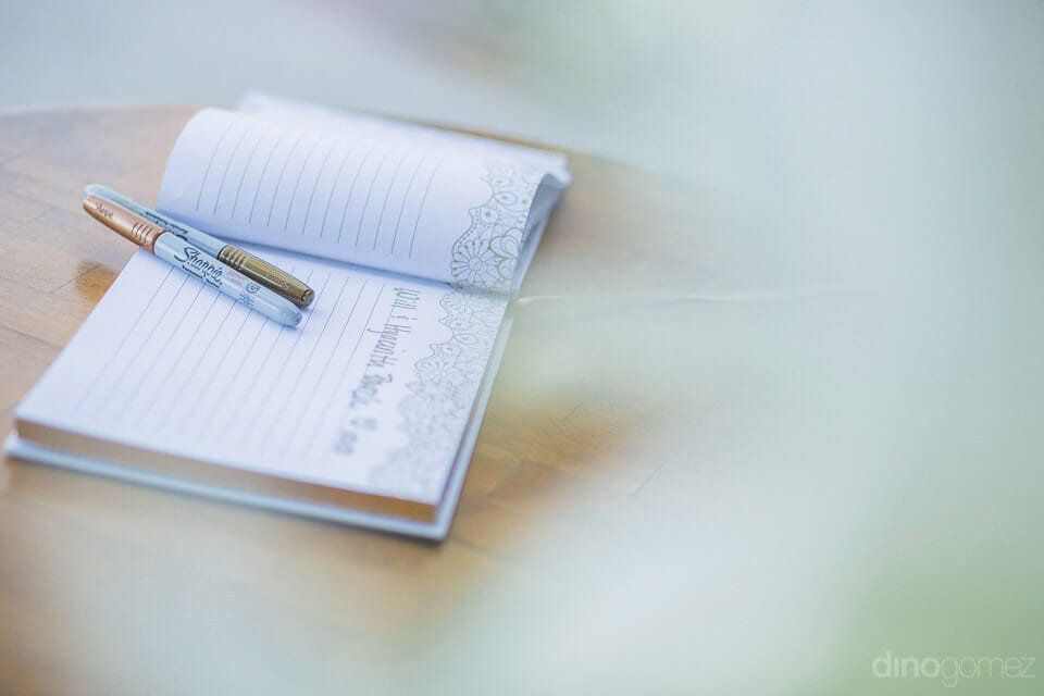 A diary with blank pages is placed on a wooden table along with two pens on the wedding day of the couple- Nicole & Ryan