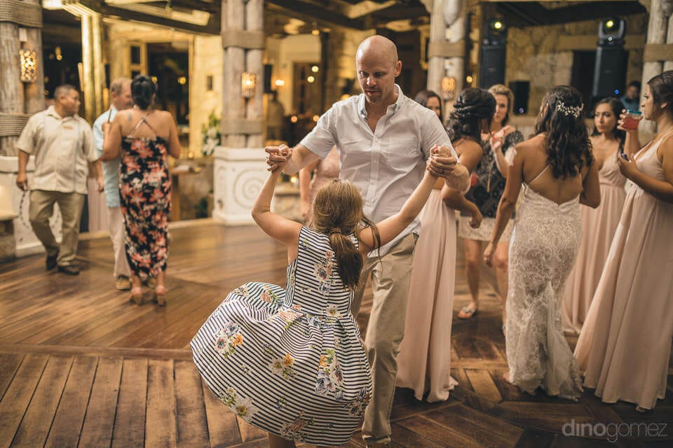 A little young girl is dancing with a gentleman along with all the wedding guests at the evening reception party of the couple- Nicole & Ryan