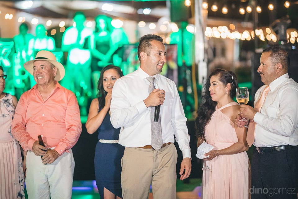 A group of wedding guests are standing at the stage during the reception party and speaking a few words for the newly married couple- Christina & Steve
