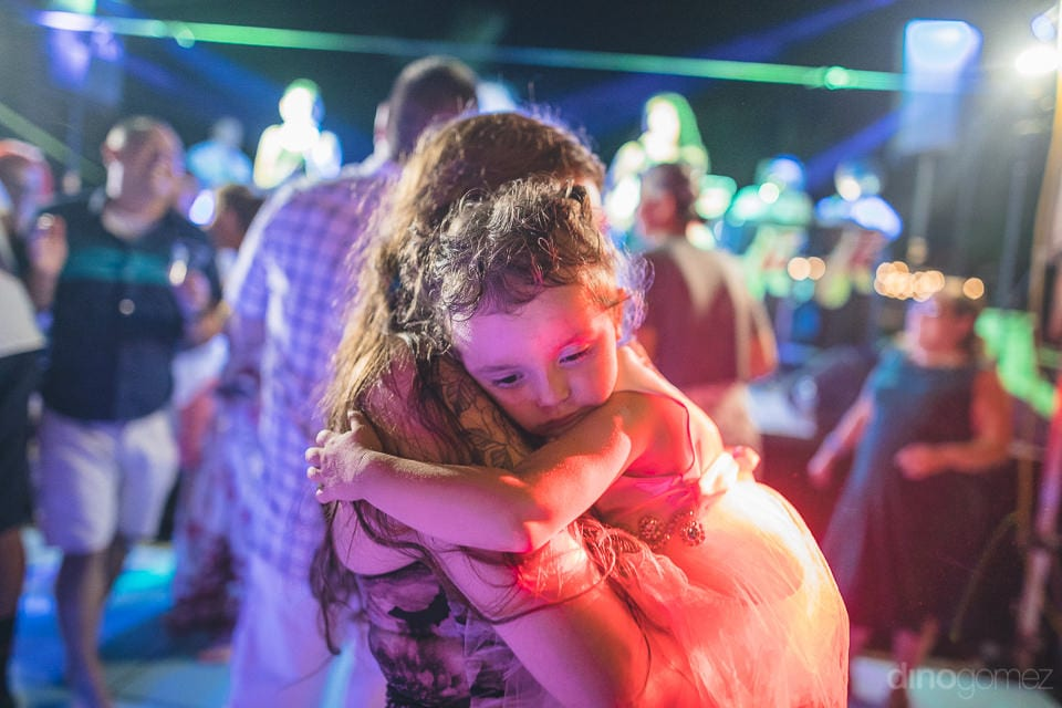 A young lady is carrying her baby girl in hands during the reception party- Christina & Steve