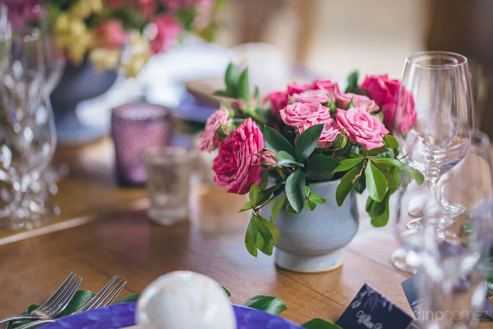 A white colored vase is placed on the top of a table with pink roses in it along with other pieces of decoratives for the wedding party of lovely couple- Nicole & Ryan