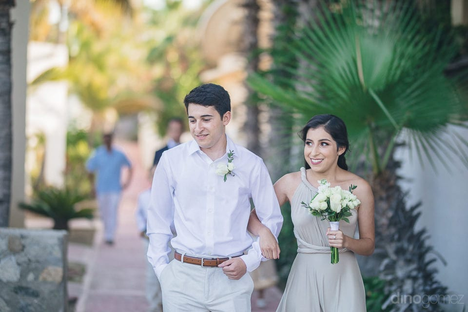 A young couple holding each others hands is walking towards the wedding stage wearing broad smile- Christina & Steve