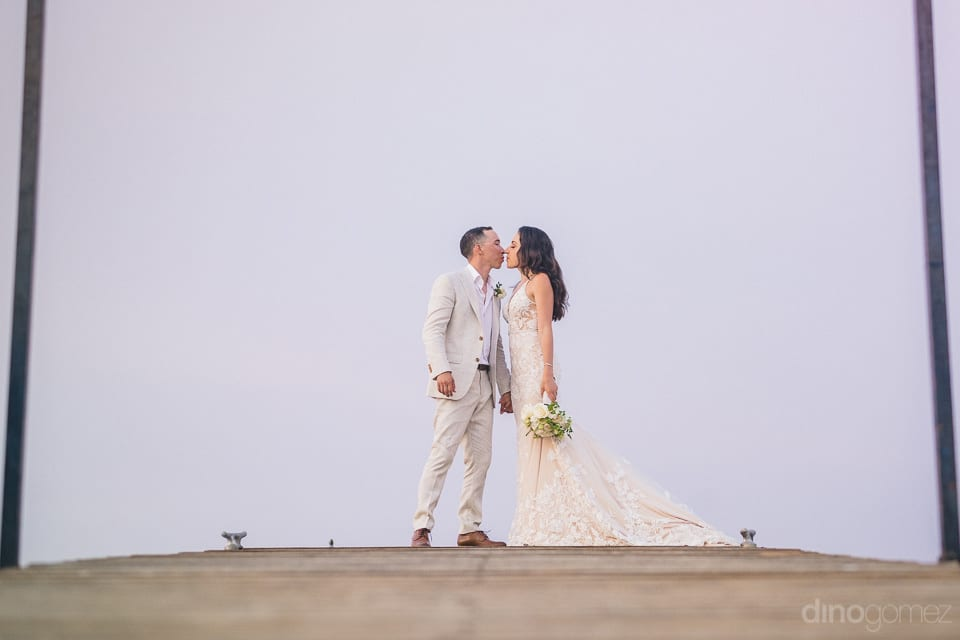 Newly married couple is standing on a wooden floor and is posing beautifully for the camera- Christina & Steve