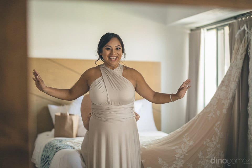 A Lovely Lady Is Happily Posing For The Camera While Getting Dressed For The Wedding Of The Lovely Couple- Christina & Steve
