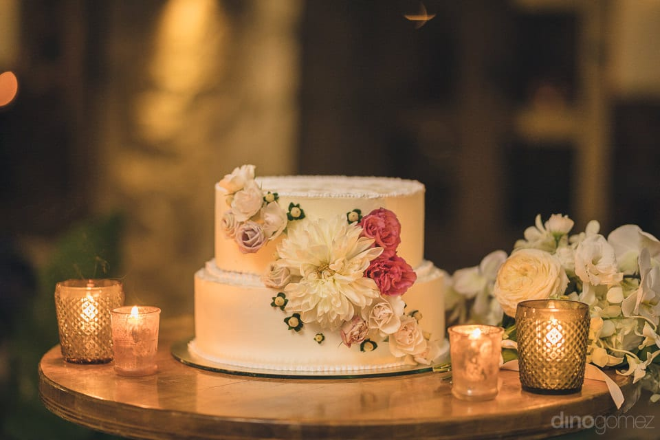 A beautiful white wedding cake of the lovely couple is decorated with colorful flowers- Nicole & Ryan