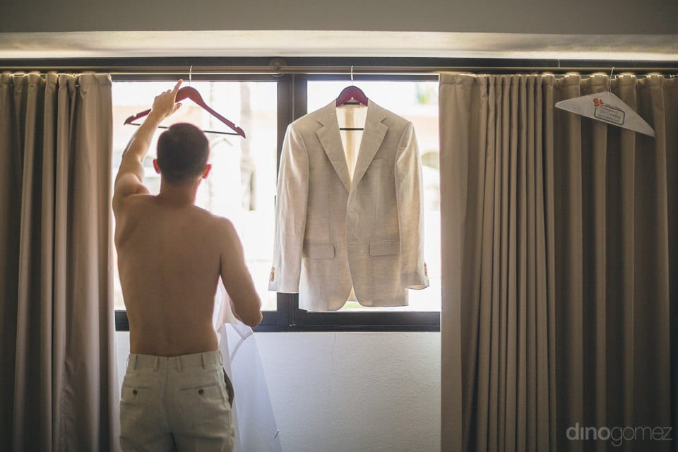 A young man is standing with his back facing the camera while getting dressed for the wedding- Christina & Steve
