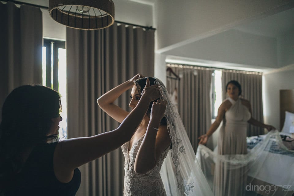 The bride is setting her beautiful head veil decorated with the crystals for the wedding- Christina & Steve