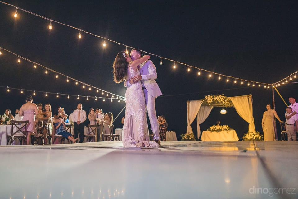 Lovely couple is kissing each other standing on the dance floor under the romantic dark sky during the reception party- Christina & Steve