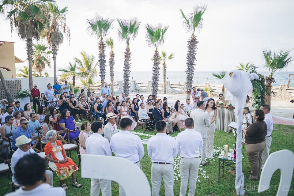 All the wedding guests are sitting on the chairs at the beach side during the wedding ceremonies of the lovely couple- Christina & Steve