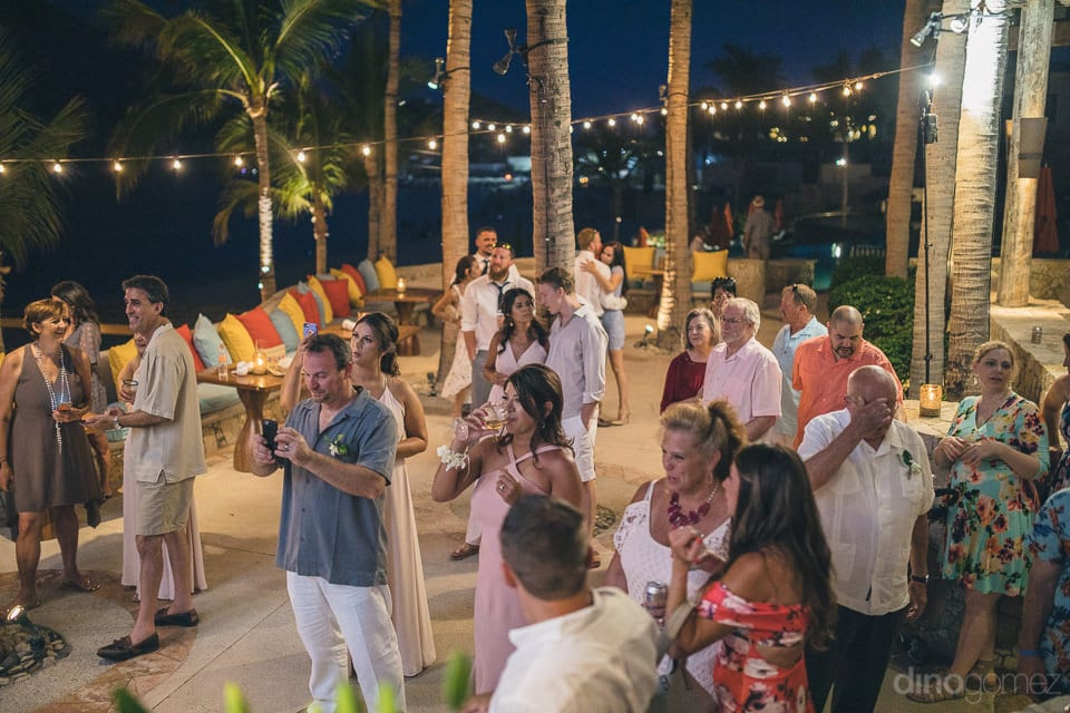 All the wedding guests are standing together at the reception hall under the beautiful yellow lights at the beach side- Nicole & Ryan