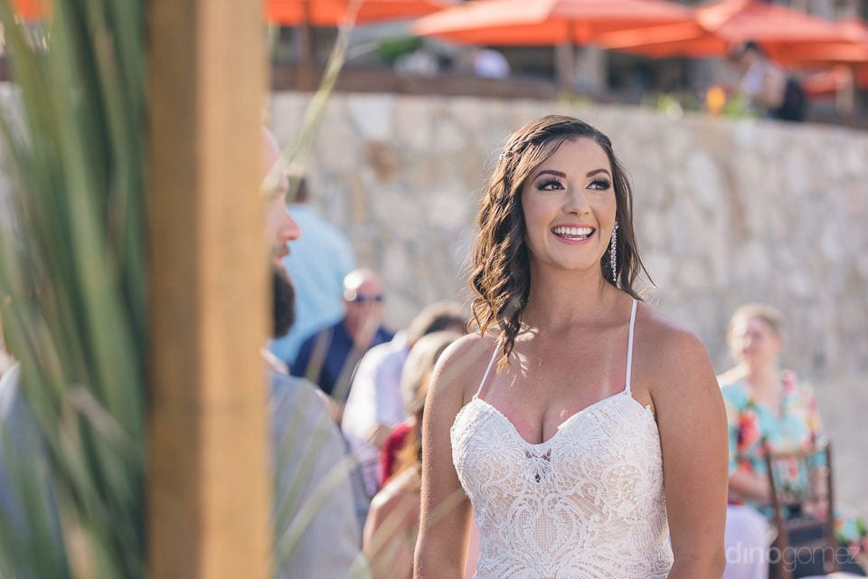 Lovely bride in cream laced gown and big hanging earings is looking gorgeous with a big smile on her face- Nicole & Ryan
