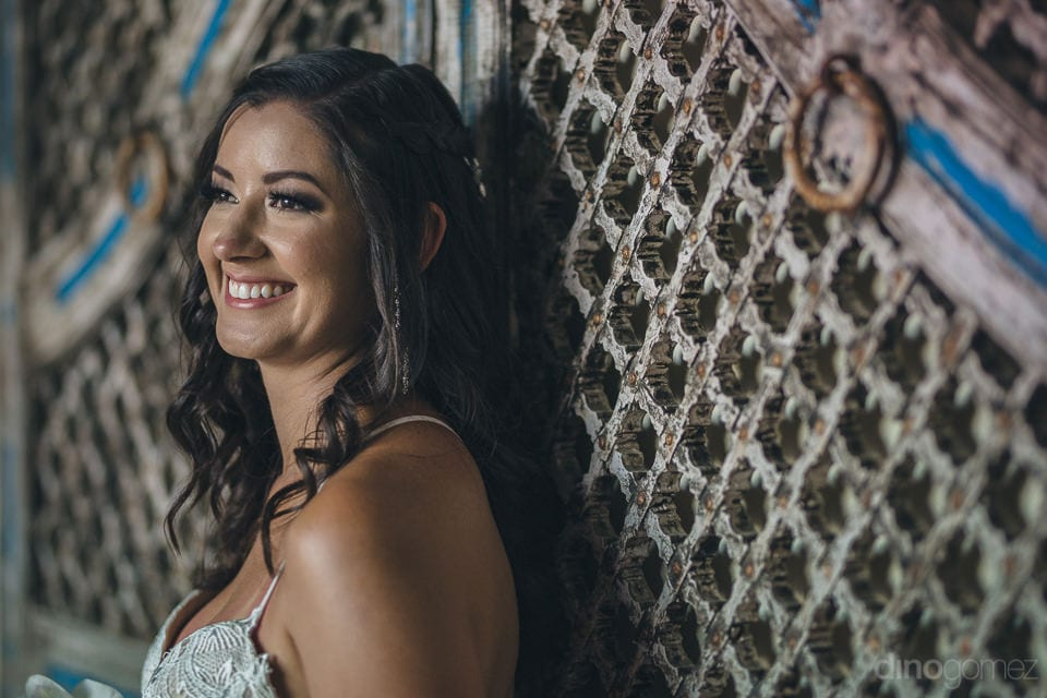 Lovely bride is giving a striking pose infront of an antique door after the completion of wedding ceremonies- Nicole & Ryan