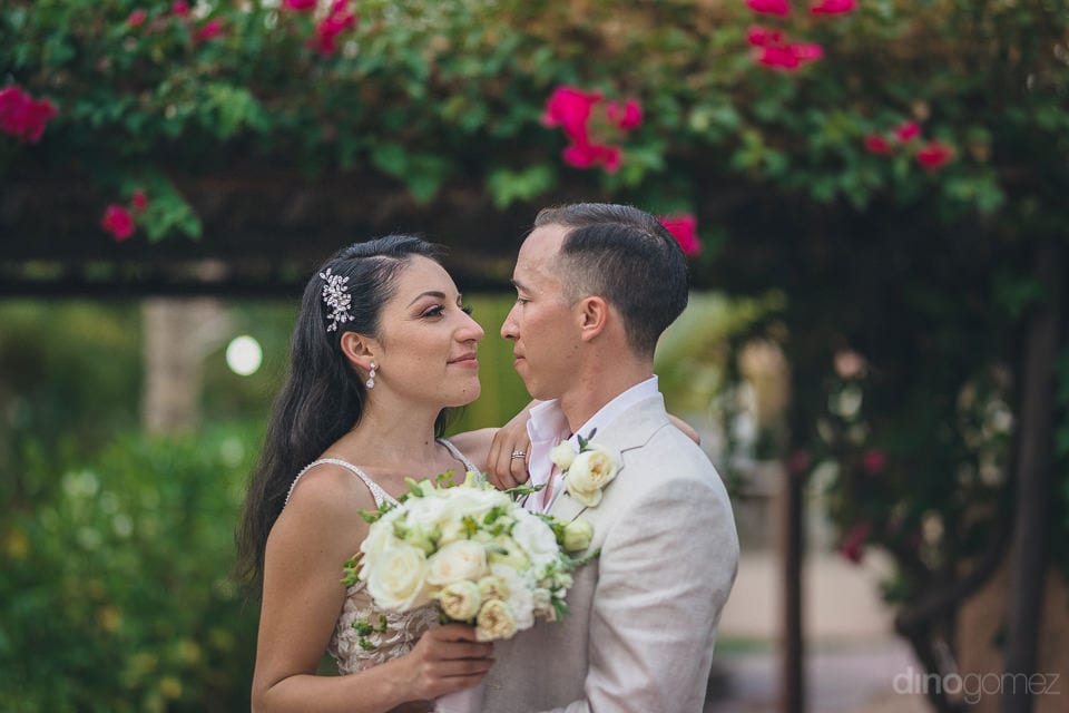 Newly Married Couple Is Holding Each Other While Standing In The Lush Green Garden- Christina & Steve