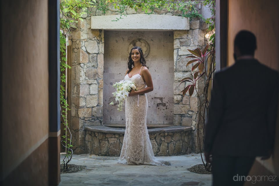The bride is looking fantastic posing infront of a stone wall while holding a bouquet in her hands- Nicole & Ryan