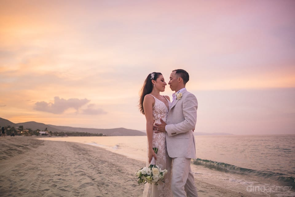 Newly married couple is standing on golden sand and is giving a romantic pose during the sunset for the camera- Christina & Steve