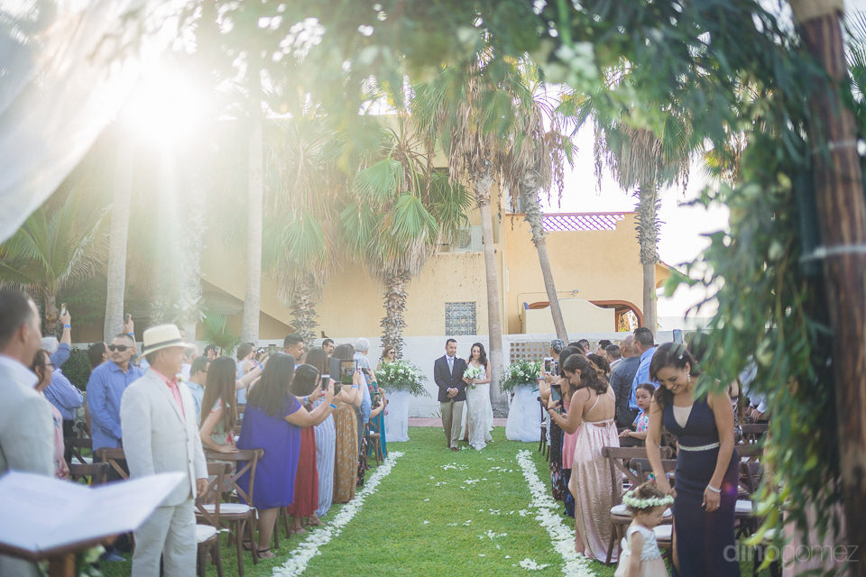 Ravishing bride is walking towards the wedding stage holding arms of a gentleman with all the smiles on her face- Christina & Steve