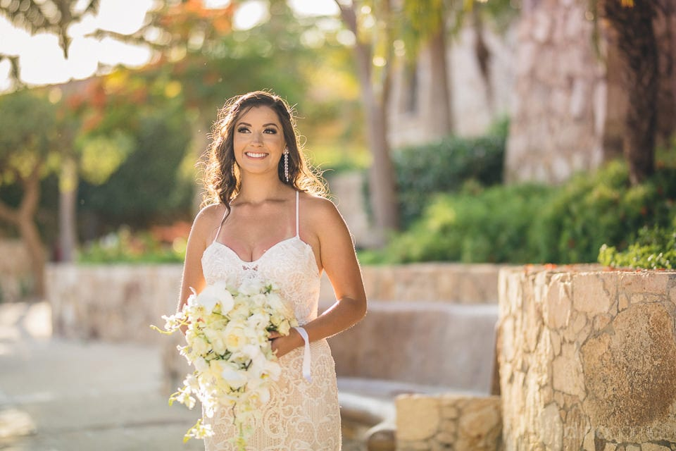 The bride is giving a striking pose for the camera standing under the shinning sun and holding her wedding bouquet- Nicole & Ryan