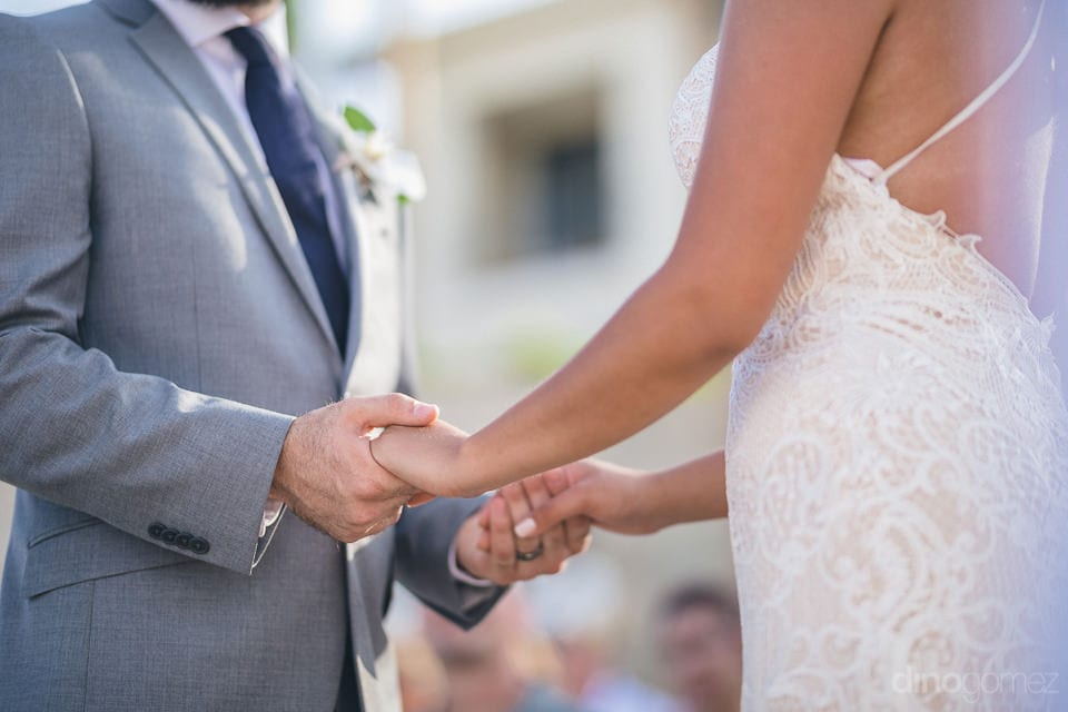 A picture of the couple holding each others hands during the wedding ceremony- Nicole & Ryan