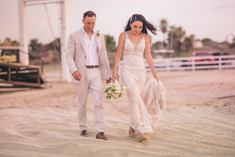 The couple is walking and talking to each other on the golden sand during the sunset- Christina & Steve
